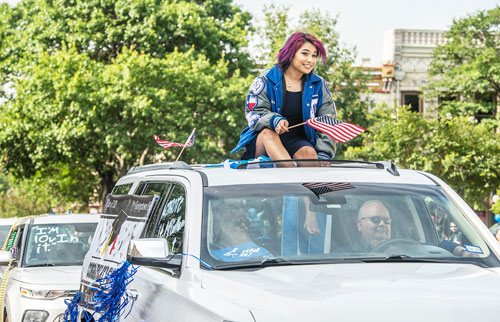 A girl with purple hair sits atop an SUV while waving an American flag. Inside the car a smiling man is seen driving.