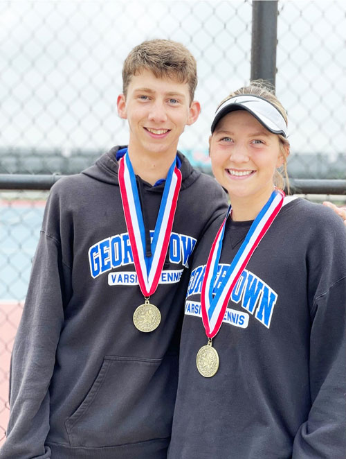 A teenage boy stands with arm around his teenage sister. Both wear championship medals and Georgetown ISD sweatshirts.